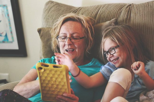 child and mom using tablet